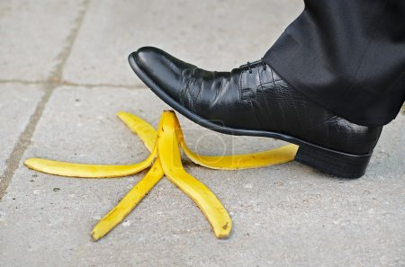 Businessman about to slip and fall on a banana ski...