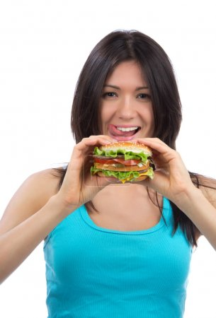 Woman with tasty fast food unhealthy burger in hand hungry