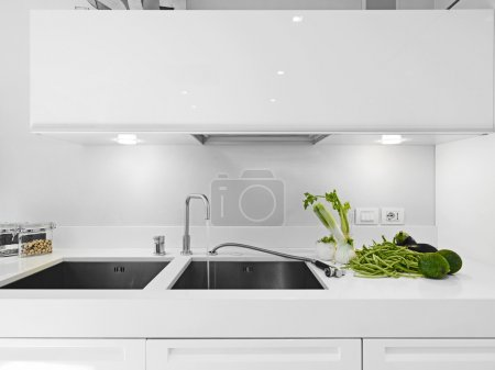 Vegetables near the faucet in the modern white kitchen