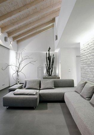 Photo pour Canapé gris moderne dans la chambre sous les toits avec plafond en bois - image libre de droit