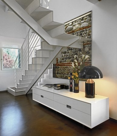White cabinet next to the iron staircase in modern living