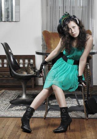 Photo pour Jolie fille dans une robe verte assis dans un salon à la maison - image libre de droit
