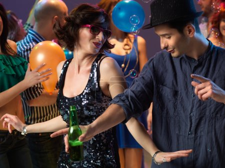 Photo for Happy, young couple flirting and dancing on the dancefloor in a night club - Royalty Free Image