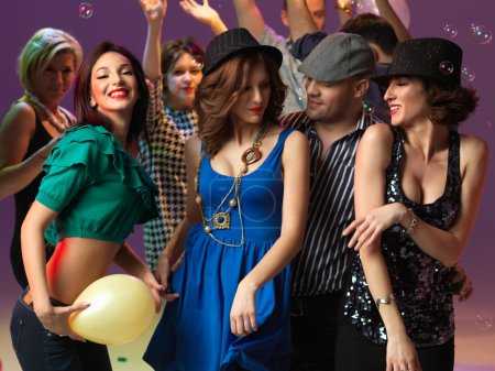 Photo for Happy, young flirting and dancing on the dancefloor, in a night club - Royalty Free Image