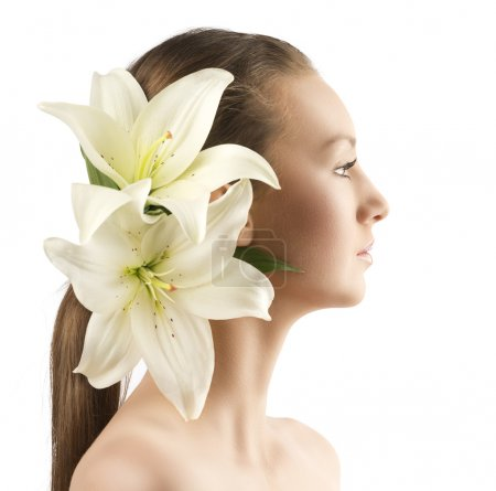 Photo for Beauty portait of pretty young girl with lilies, the girl is turned in profile at left and has lilies in the hair near the right ear - Royalty Free Image