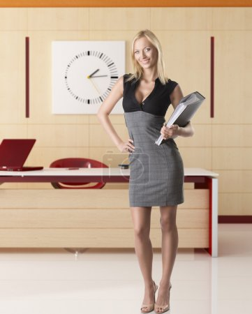 Photo for Pretty business woman with elegant dress and classifier, she is in front of the camera and smiles, takes the classifier with left hand - Royalty Free Image