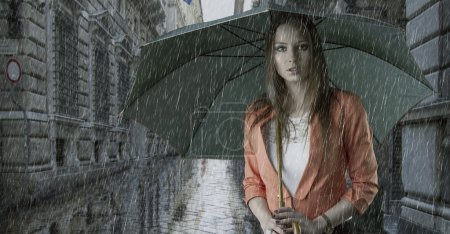 Photo for Pretty young woman with green umbrella, under the rain falling down in a old fashion street - Royalty Free Image