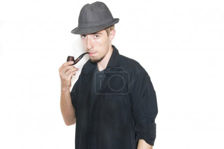 Man in black shirt with tobacco pipe on isolated background looks into the eyes