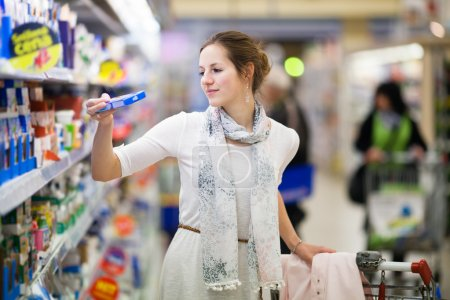 Photo for Beautiful young woman shopping for diary products at a grocery store/supermarket (color toned image) - Royalty Free Image