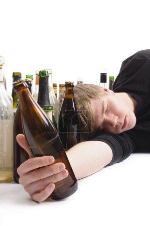 Photo pour Junger mann mit kurzen blonden haaren liegt auf dem boden und ist von vielen leeren bier-und schnapfsflaschen umgeben, oberperspektive. - image libre de droit