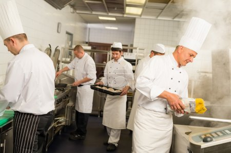 Photo for Professional kitchen busy team cooks and chef prepare meal - Royalty Free Image