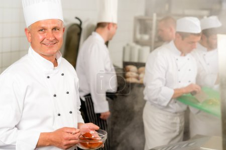 Professional kitchen smiling chef add spice food