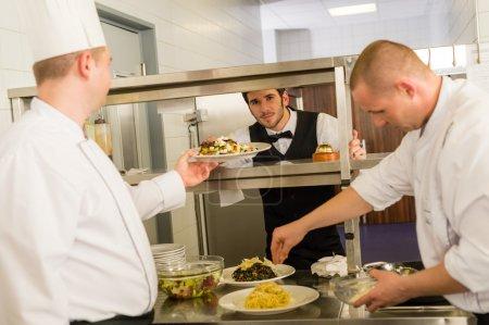 Photo pour Cuisinier professionnel préparer service alimentaire donner des repas au serveur - image libre de droit