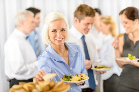Photo for Smiling business woman during company lunch buffet hold salad plate - Royalty Free Image