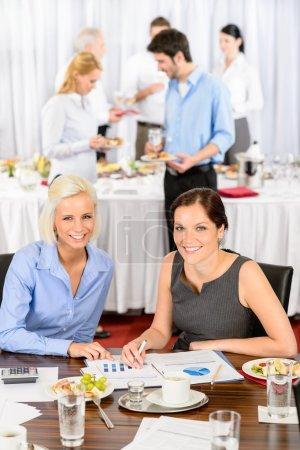 Photo pour Deux femmes d'affaires à la réunion de la société travaillent pendant le déjeuner buffet - image libre de droit