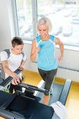 Mladý fitness instruktor žena běží v tělocvičně
