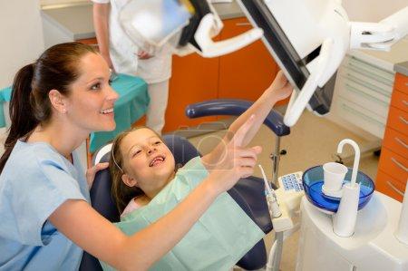 Photo pour Sourire dentiste et enfant pointant au bureau de stomatologie de l'écran - image libre de droit