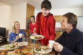 Užitečné dospívající děti slouží potravin rodičům v kuchyni