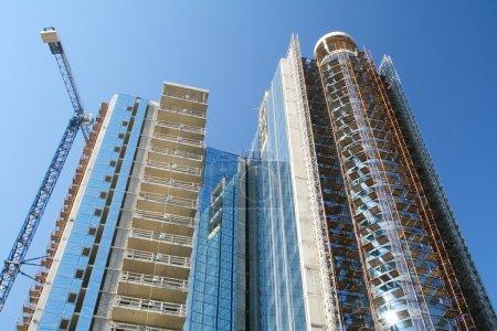 Photo pour Bâtiment moderne de grande hauteur en construction sur fond de ciel bleu . - image libre de droit