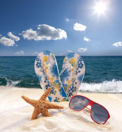 Photo pour Étoile de mer, lunettes de soleil et tongs sur la plage - image libre de droit