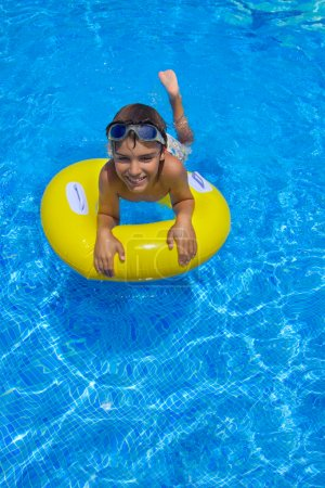 Boy swimming on rubber ring in pool