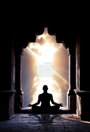Photo for Yoga meditation in lotus pose by man silhouette in old temple arch at dramatic sky background. Free space for text - Royalty Free Image
