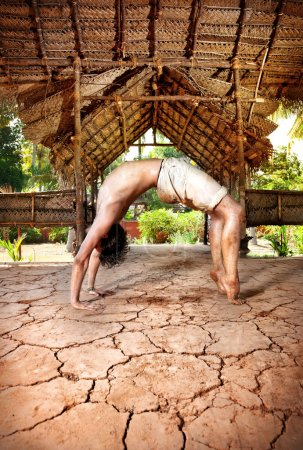 Photo for Yoga chakrasana wheel pose by fit man in white trousers on the drought earth in yoga shala, Varkala, Kerala, India - Royalty Free Image