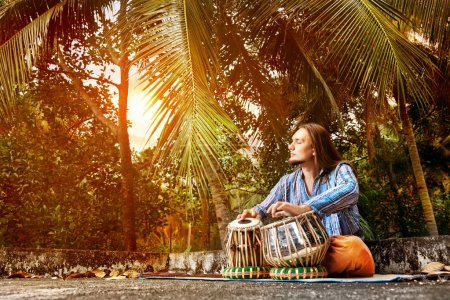 Photo pour Homme qui joue à la batterie de tabla indien traditionnel au coucher de soleil fond tropic - image libre de droit