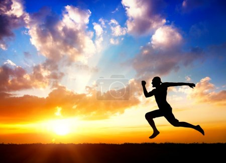 Photo for Silhouette of man running towards the sun at cloudy background - Royalty Free Image