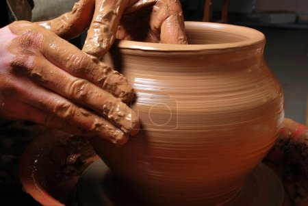 Photo for Hands of a potter, creating an earthen jar on the circle - Royalty Free Image