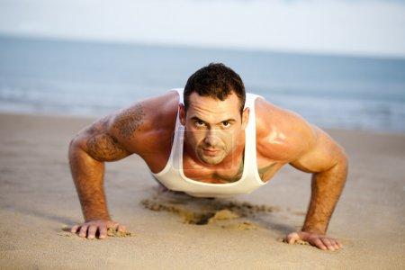 Man doing push ups on a beach