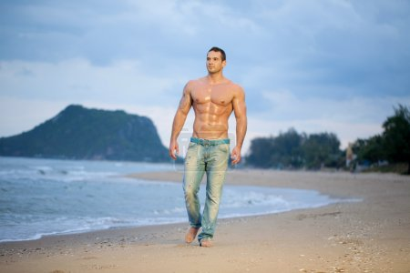 Muscular male walking along a beach