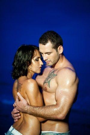 Photo pour Jeune adulte couple seins nus embrassant sur la plage - image libre de droit