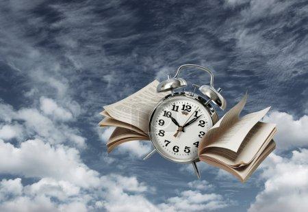 Photo pour Vieux réveil volant avec page ailes, le temps passe vite concept - image libre de droit