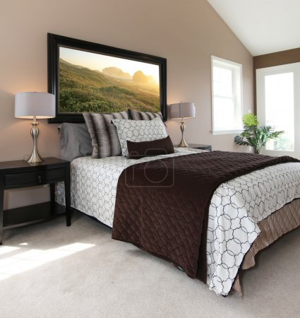 Modern brown and white bed with nightstands.