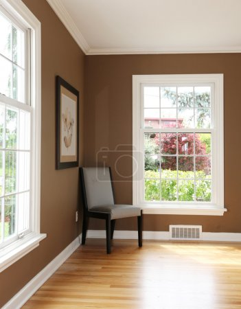 Living room corner with chair and two windows.