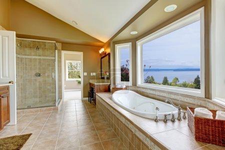 Photo pour Grand bain tun avec vue sur l'eau et intérieur de salle de bain de luxe dans des couleurs beige . - image libre de droit