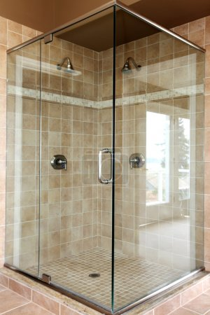 Modern new glass walk in shower with beige tiles.