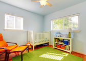 Baby nursery room design with green rug, blue walls and orange chair.