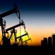 Silhouettes of oil pumps placed one after another ...