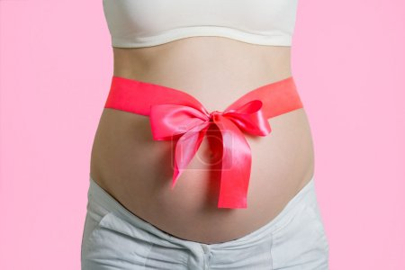 Beautiful young pregnant woman with ribbon. Isolated on pink bac