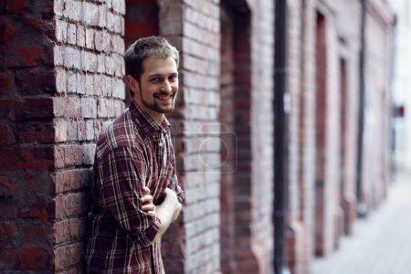 Photo pour Souriant jeune homme appuyé contre le mur de briques, il porte une chemise à carreaux et un jean - image libre de droit