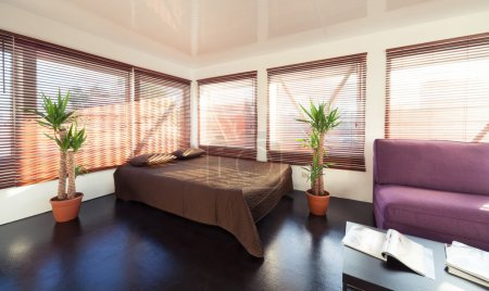 Photo pour Chambre loft moderne avec beaucoup de lumière naturelle : un lit double et un canapé confortable avec table basse - image libre de droit