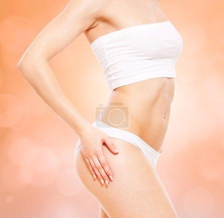 Healthy woman's body in white underwear over blurred background