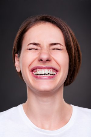 Photo for Emotional woman is laughing loudly over dark background - Royalty Free Image