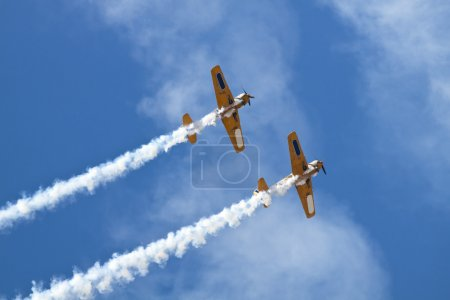 Group of old timer planes performing acrobatics in the air