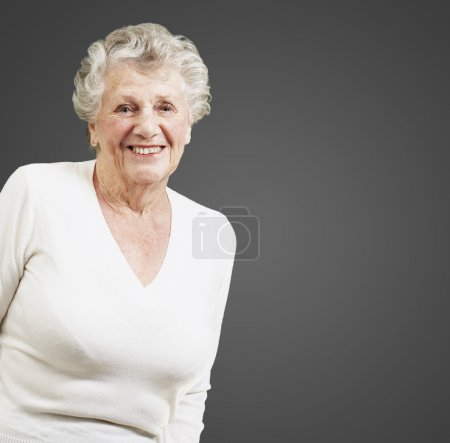Photo for Pretty senior woman smiling against a black background - Royalty Free Image