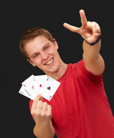 Portrait of young man doing a victory gesture playing poker over