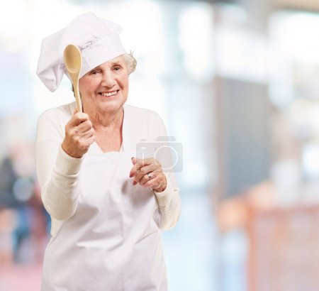 Portrait of senior cook woman holding a wooden spoon indoor