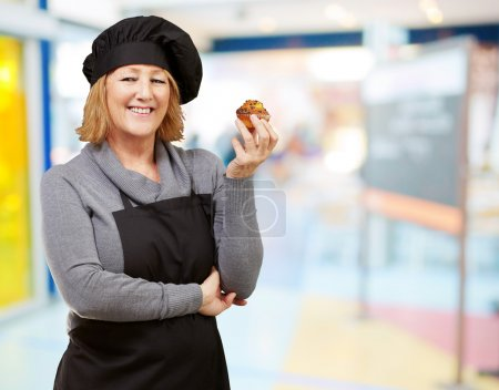 Photo for Portrait of middle aged cook woman holding a homemade muffin indoor - Royalty Free Image